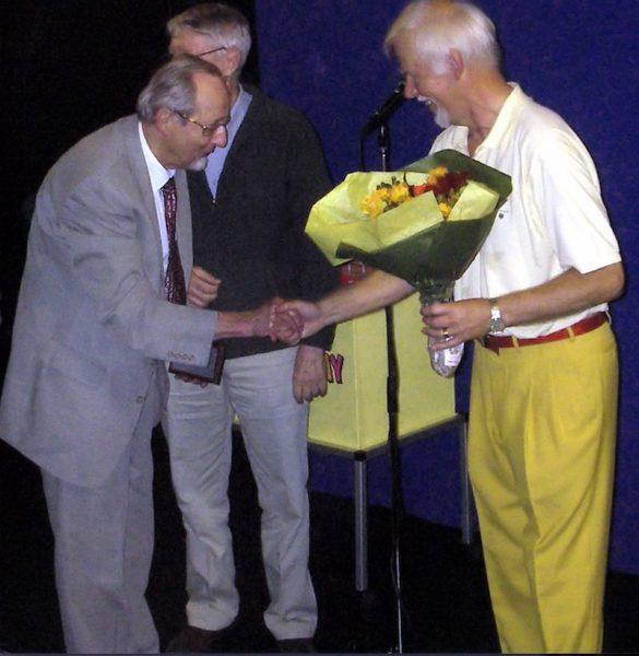 Sekreteraren Lennart Gombrii överlämnar blommor. I bakgrunden ordförande Tom Fahlén. Foto Torbjörn Hellgren